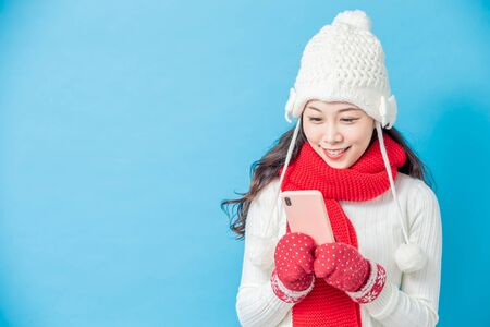 asian woman wear winter clothes and use smartphone isolated on blue background