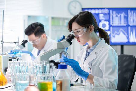 Equipo científico asiático utiliza microscopio en el laboratorio.