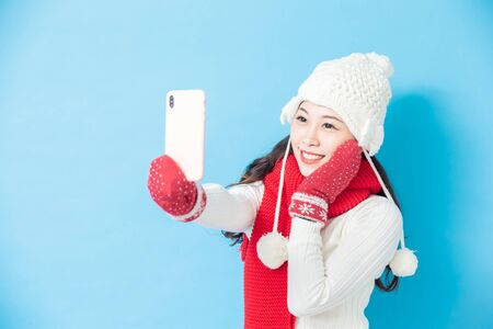asian woman wear winter clothes and take selfie isolated on blue background Фото со стока