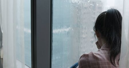 asian woman cry and sit by window on a rainy day