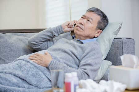 asian eldely man get sick and fever with thermometer lying on the sofa at home