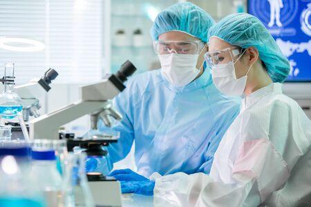 Asiatisches Biotechnologie-Forschungsteam sieht Computer aus und trifft sich mit Reinraumkleidung in der Fabrik Standard-Bild