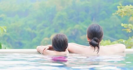 rear view of asian mother and daughter enjoy outdoor hot spring Stok Fotoğraf