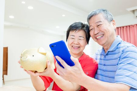Perfect Retire plan concept - eldely couple hold piggy bank and smartphone happily at home