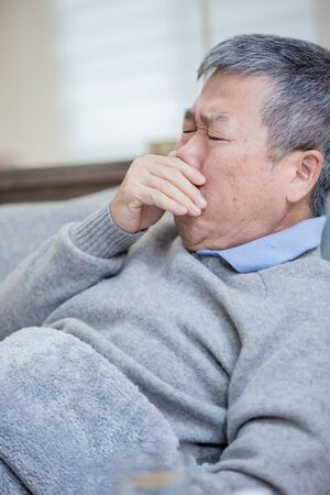 asian eldely man get sick and cough lying on the sofa at home