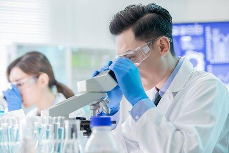 asian scientist team use microscope in the laboratory 写真素材