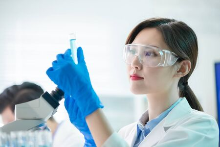 asian female scientist hold a test tube filled with liquid in the laboratory