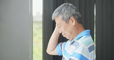 asian elder man wory something and look through window  Stock Photo
