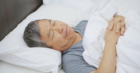 asian elder man tossed and turned all night 免版税图像