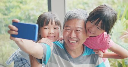 asian elder grandfather take selfie with kids happily 免版税图像