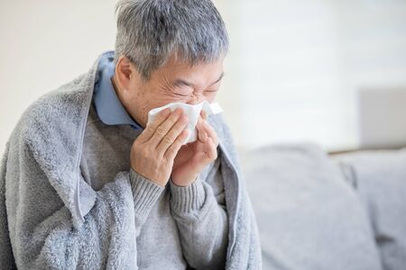 old asian man get a cold and sneeze with tissue paper at home