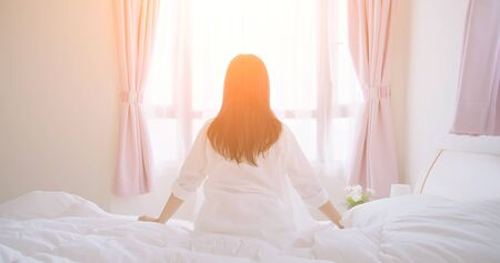 back view of woman sit on bed and look out windows after wake up in the morning at home