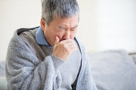 asian eldely sick man has a cold and cough at home