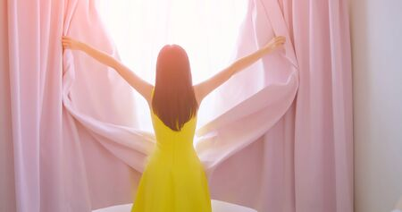 back view of fashion young lady opening curtains and look outside through window