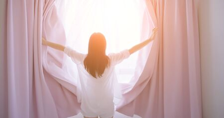 woman opening curtains and look outside through window in the morning while traveling