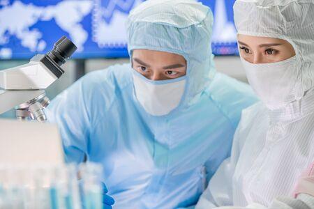 il team di ricerca biotecnologico asiatico guarda incontro al computer con abiti da camera bianca e conduce esperimenti in laboratorio