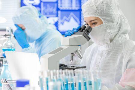 El equipo asiático de investigación en biotecnología mira el microscopio con ropa de sala limpia y realiza experimentos en el laboratorio.