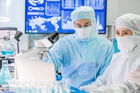 El equipo asiático de investigación en biotecnología busca una reunión de computadora con ropa de sala limpia y realiza experimentos en el laboratorio.