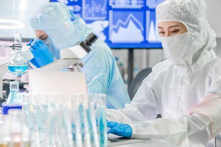 Komputer typu azjatyckiego naukowca z kombinezonem do pomieszczeń czystych w laboratorium Zdjęcie Seryjne
