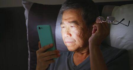 asian elder man has farsighted so he takes off glasses when using smartphone Reklamní fotografie
