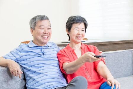 eldely couple sit on the sofa and watch tv happily with remote control