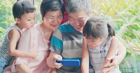 asian elder grandparents watch video by smartphone with grandchildren happily