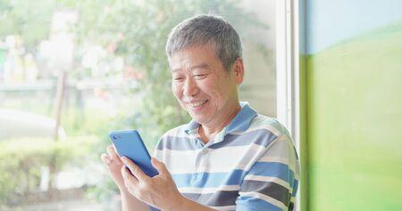 Asiatischer älterer Mann benutzt Smartphone neben Windows