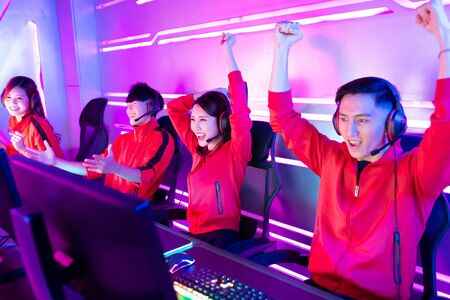 Ein Team asiatischer Cybersport-Spieler im Teenageralter gewinnt das Multiplayer-PC-Videospiel beim eSport-Turnier und jubelt mit der Hand hoch Standard-Bild
