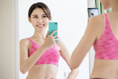 asian woman take selfie in front of mirror with sport wear happily