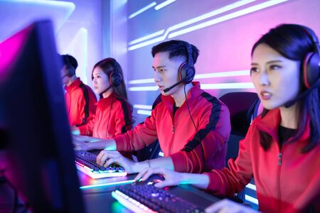 Team of asian teenage cyber sport gamers play in multiplayer PC video game on eSport tournament