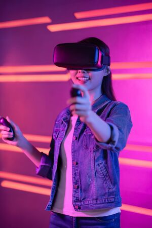 vertical of asian girl wear vr glasses and play games