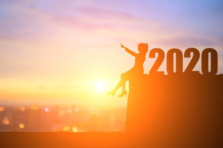silhouette of businesswoman pointing something and sit on the cliff with 2020