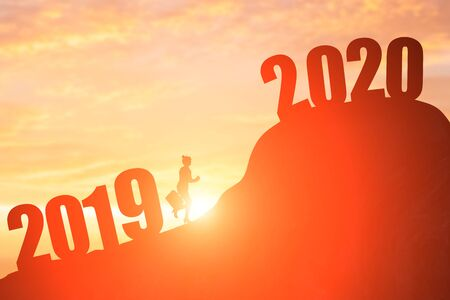 silhouette of businesswoman run on the moutain with 2020 year