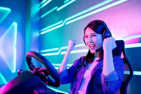 Young Asian Pro Gamer Girl Win Car Racing Online Video Game and Cheer Up with Fist Gesture