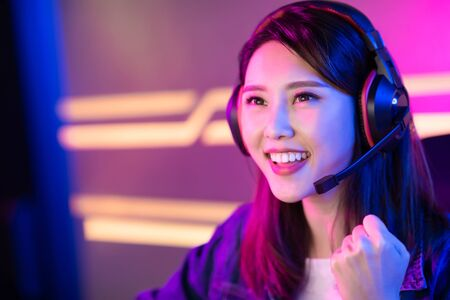 Young Asian Pretty Pro Gamer win in Online Video Game and cheer with fist gesture