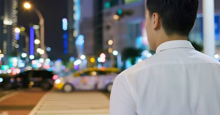 asian businessman get off work and walk on the street in the evening