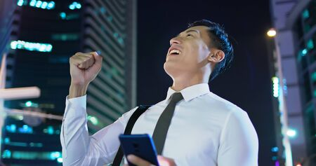businessman use the smart phone and feel excited with fist gesture