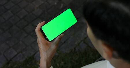 asian young businessman use 5g full display smartphone with green screen on the street