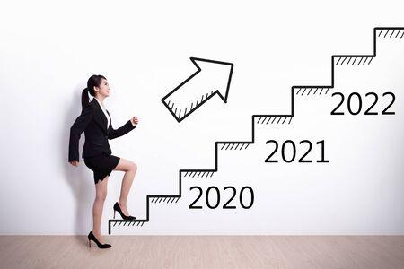 Femme d'affaires montant dans les escaliers pour remporter son succès dans la nouvelle année 2020 Banque d'images