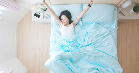 Top view of young beautiful woman wear smart watch and sleep well in the morning