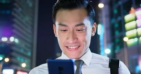 close up of asian businessman use smart phone outdoor in the evening
