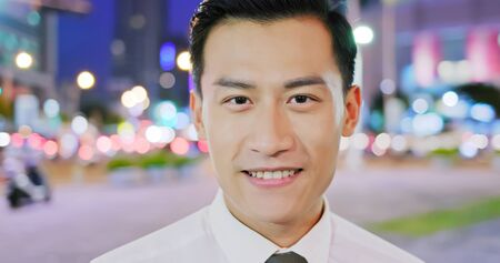 asian businessman smile to you on the street in the evening
