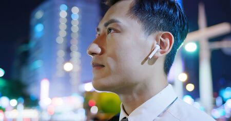 asian man wear wireless earbuds on and to listen music on the street 免版税图像