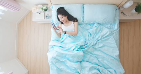 Overhead View of woman use smart phone happily and lying in the bed at home