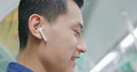 asian man use wireless earbuds to listen music on the mrt 版權商用圖片