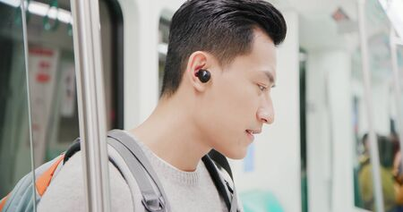 asian man use wireless earbuds to listen music on the mrt train Stok Fotoğraf