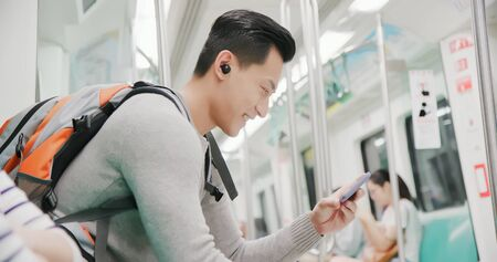 asian man use wireless earbuds to watch video on the subway 스톡 콘텐츠