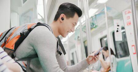 asiatischer Mann verwendet drahtlose Ohrhörer, um Videos in der U-Bahn anzusehen