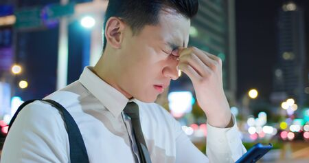 asian businessman feel eye tired while using smartphone on the street in the evening 版權商用圖片