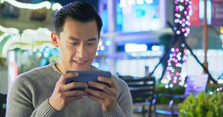 close up of asian young man play game with 5g smartphone outdoor in the evening